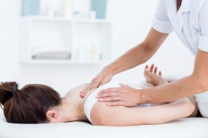 Physiotherapist doing neck massage in medical office