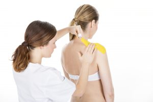 Physiotherapist applying tapes on a shoulder