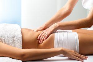 Close up of osteopath doing manipulative abdomen massage on female patient.