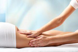 Therapist massaging upper back part of female leg. Hands applying pressure on hamstrings.