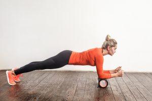 Blonde woman doing plank in foam roller. Studio shot