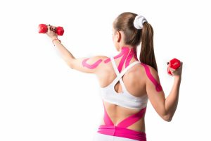 Cute young girl athlete fitness trainer holding red dumbbell in hands with pink stickers on her shoulders and neck. Concept of caring for muscles and ligaments of arms and back. Places for advertising