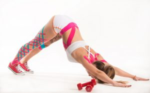 Cute slender young girl athlete in a tracksuit makes an exercise plank with colored stripes stickers on the body on a white background. Concept of muscle and joint flexibility. Advertising space